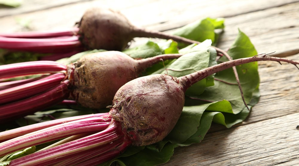 three pieces of beets on a wooden surface
