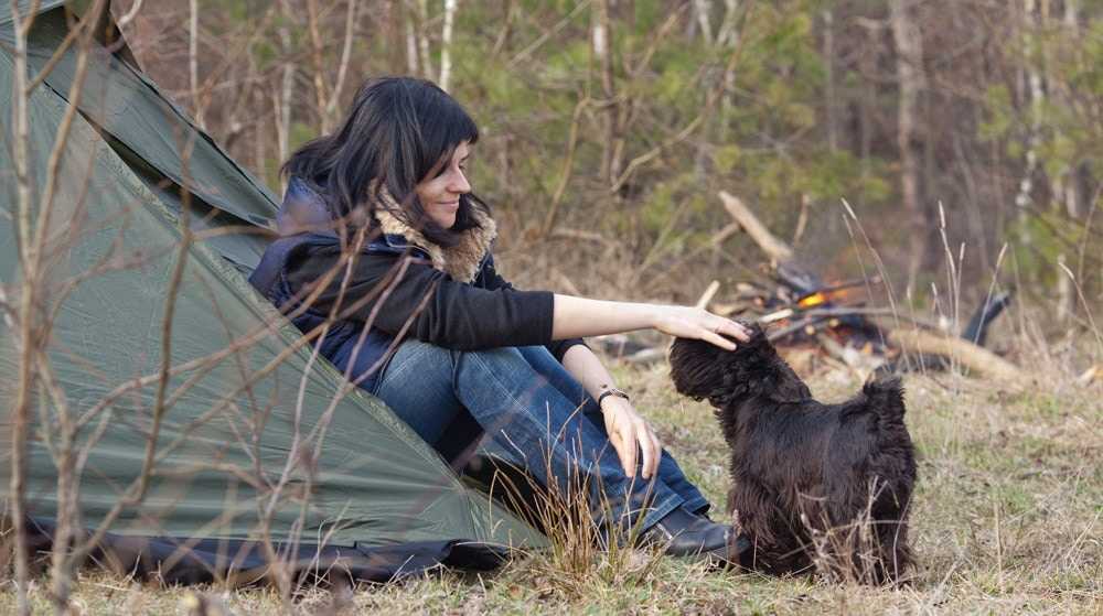 A woman stroking a dog outdoors